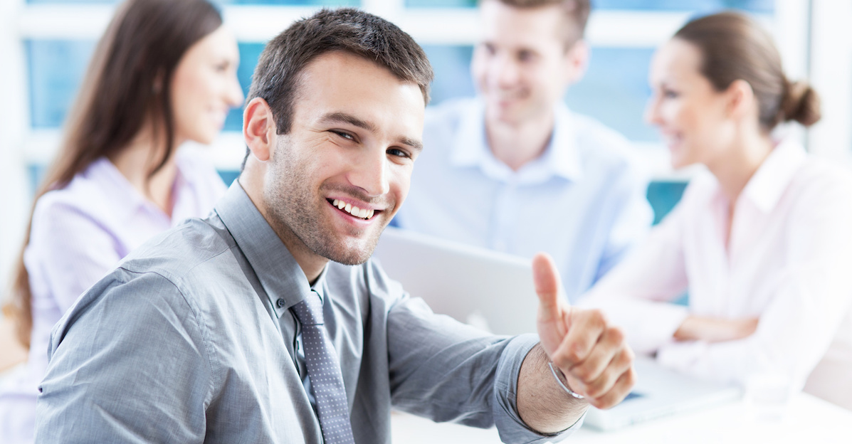 A CEO turning and giving a thumbs up after discussing employee engagement strategies with 3 of his colleagues