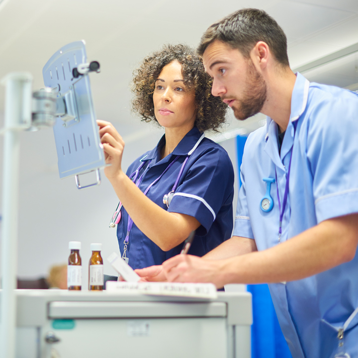 Female and male doctor standing a reviewing information in a healthcare environment