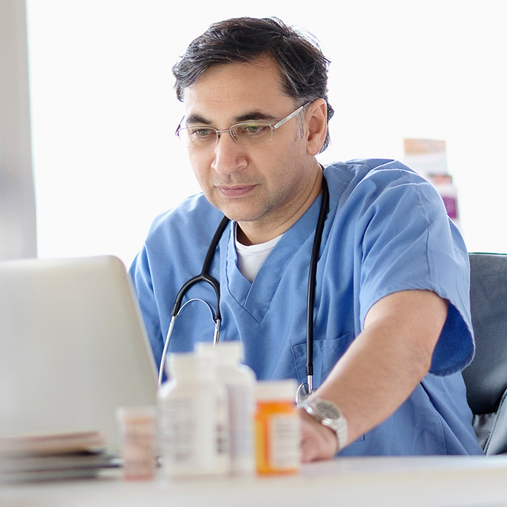 Male doctor sitting looking at patient data in PointClickCare's eMAR software with prescription medication behind it