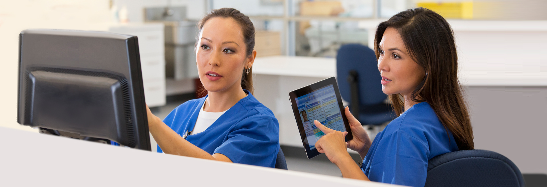 Two female skilled nursing providers looking at point of care data in PointClickCare's software on both a tablet device and desktop computer