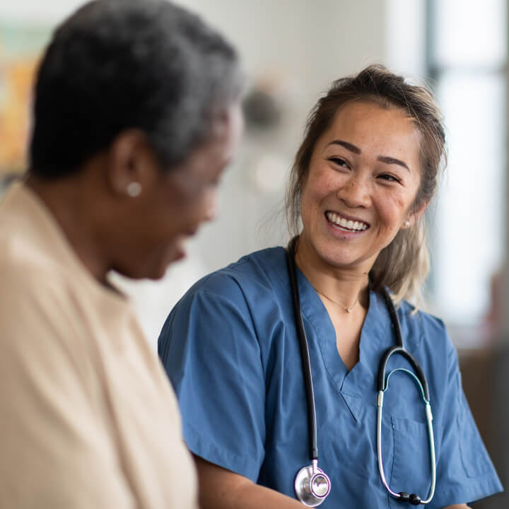 Female skilled nursing provider with a stethoscope around her neck seated and smiling with an elderly female resident