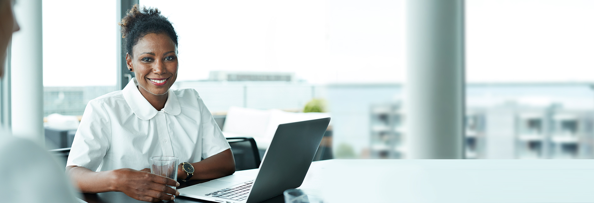 Female business professional sitting in a meeting room smiling with a glass of water in her hand and a laptop in front of her