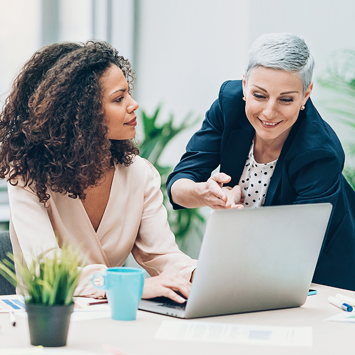 Two female business professionals reviewing payment information on a laptop