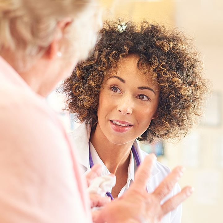 A Registered Nurse speaking to an elderly resident at a Skilled Nursing Facility