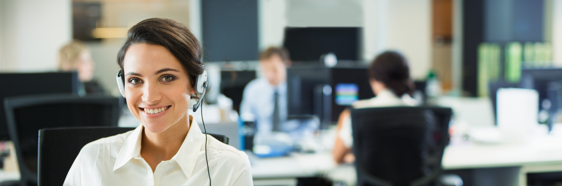 Female customer support representative smiling with a headset on with a blurred background office environment