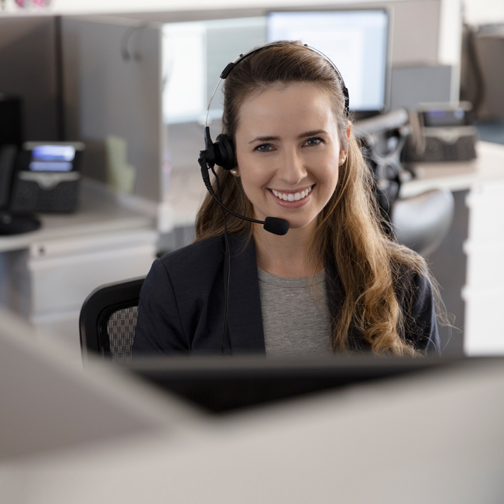 A PointClickCare support representative helping a customer on the phone.