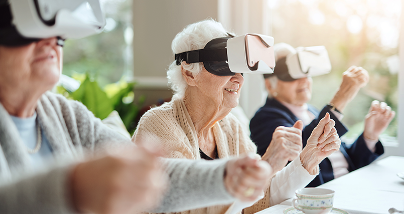 Three seniors smile while using virtual reality headsets