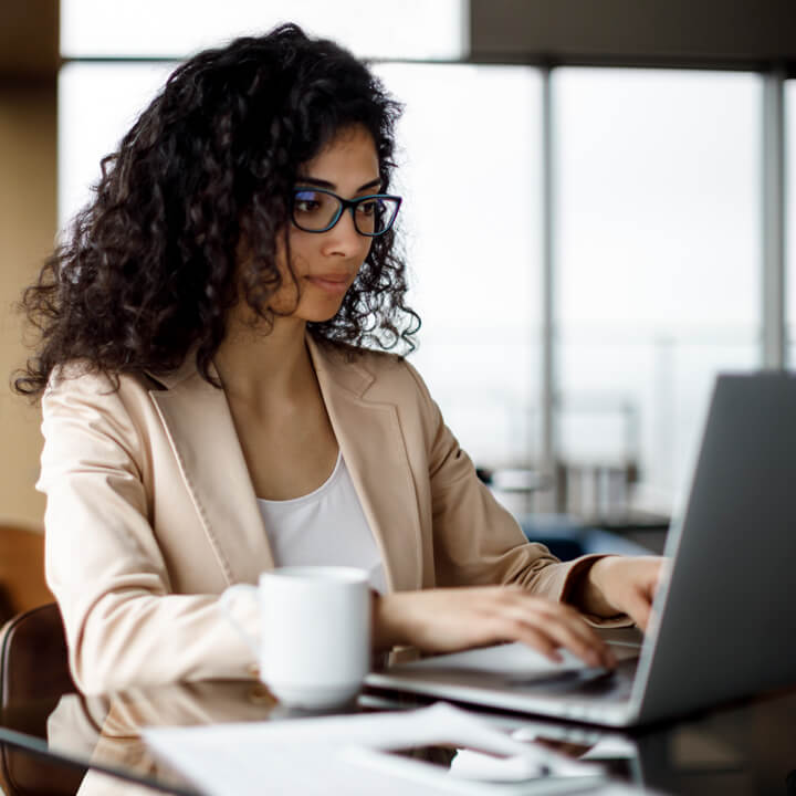 Female healthcare provider seated with her laptop and a coffee mug using PointClickCare's SmartZone for product training