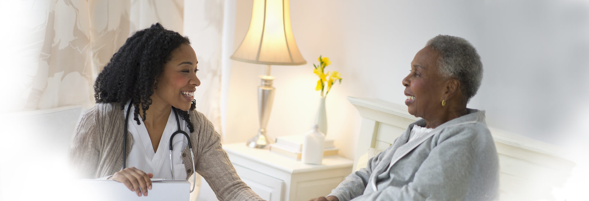 A Home Health registered nurse speaking with an elderly client in her bedroom.