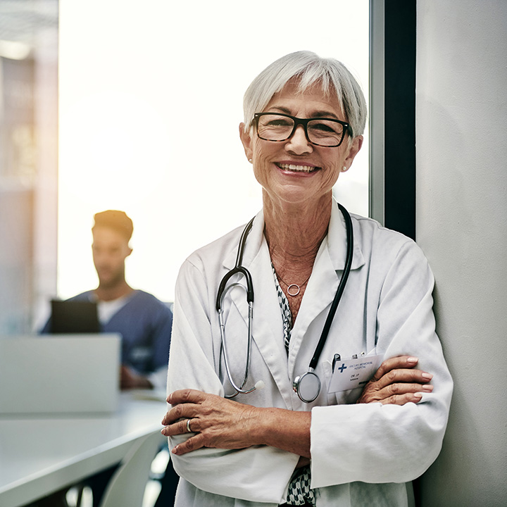 A doctor leaning against a wall and an out of focus nurse sitting at a table in the background
