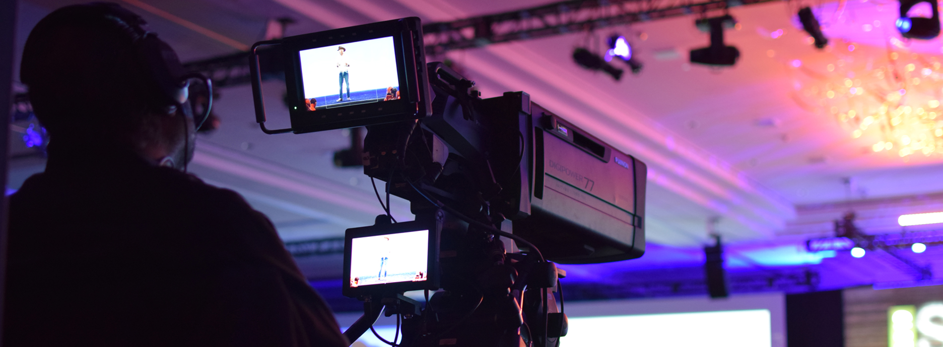 A cameraman operating a video camera and recording Dave Wessinger on Stage and SUMMIT 2019