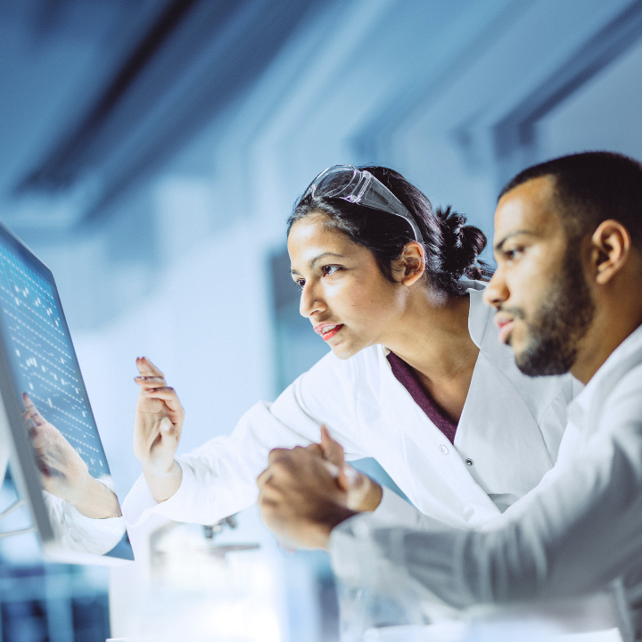 Male and female engineers in white lab coats reviewing data together on a large monitor